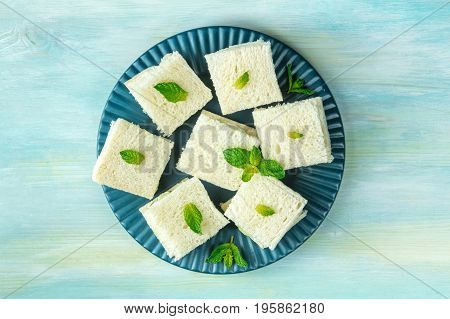 An overhead photo of a plate of cucumber sandwiches, shot from above on a teal blue texture with a place for text