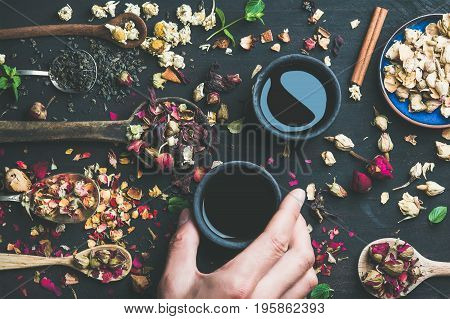 Chinese black tea in black stoneware cups, man's hand holding one cup and wooden spoons with dry herbs, flower buds and leaves over black wooden background, top view, horizontal composition