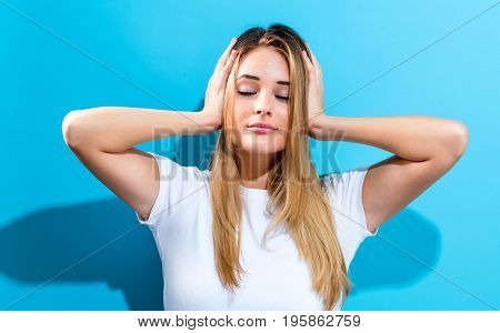 Young woman blocking her ears on a blue background