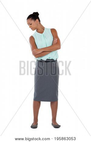 Thoughtful businesswoman standing with arms crossed against white background