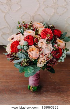 Beautiful wedding bouquet of red roses, pink flowers and greenery is on the wooden floor. Close-up