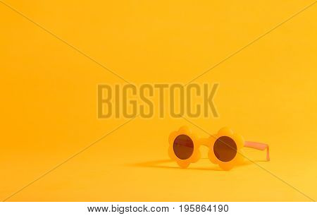 Sunflower shaped sunglasses on a yellow background