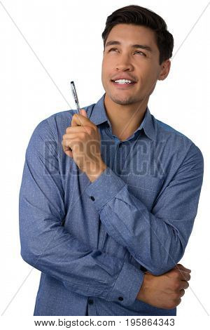 Happy thoughtful businessman holding pen while looking away against white background