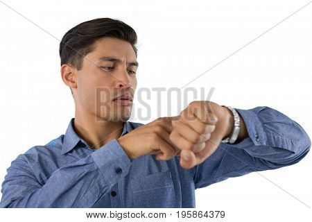 Creative businessman looking at wristwatch while standing against white background