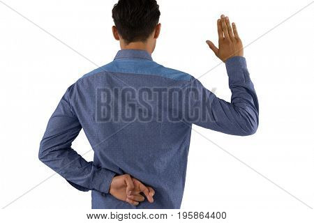 Rear view of businessman waving hand with crossed fingers while standing against white background