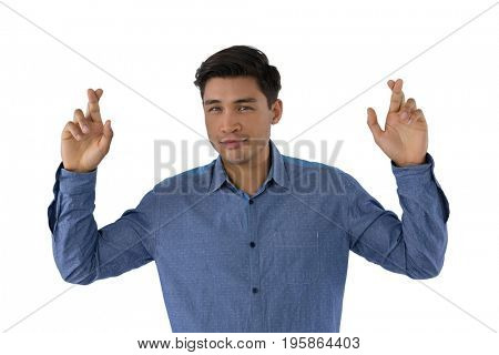 Portrait of businessman with fingers crossed standing against white background