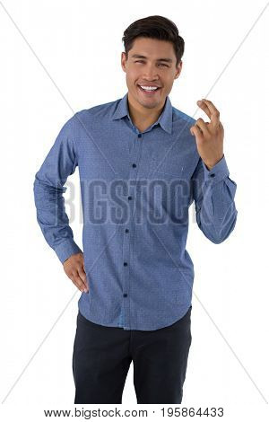 Portrait of smiling businessman showing crossed fingers while standing against white background