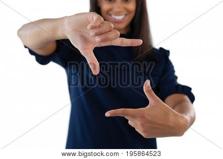 Smiling female executive forming a finger frame against white background