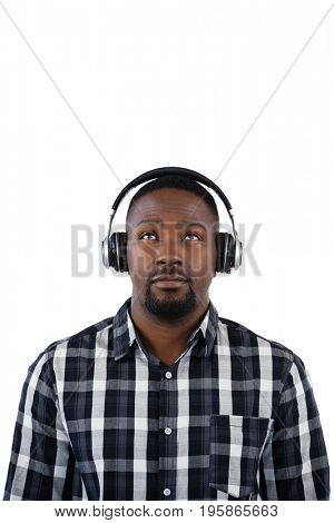 Thoughtful man listening to music on headphones against white background