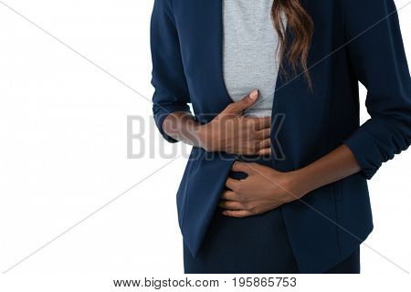 Mid section of woman suffering from stomach ache standing against white background