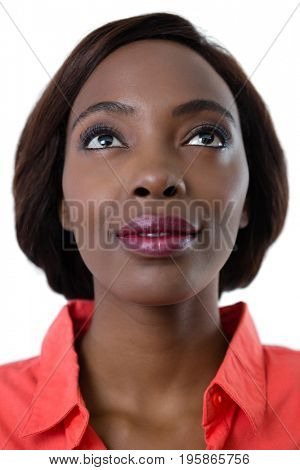 Close up of young woman looking up against white background