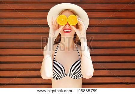 Summer Sunny Portrait Smiling Woman Holds In Hands Oranges And Hides His Eyes On Wooden Background