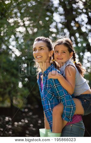 Thoughtful smiling mother piggybacking daughter against trees in backyard