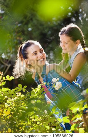 Smiling mother giving piggyback ride to daughter by plants in yard on sunny day