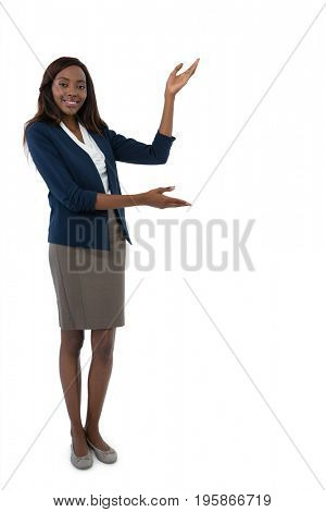 Full length portrait of businesswoman gesturing during presentation against white background