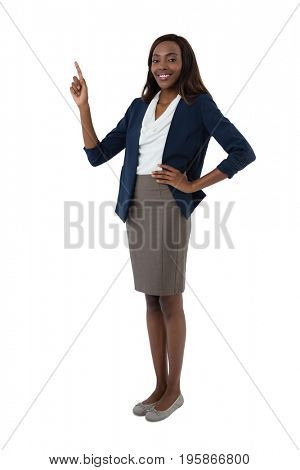 Portrait of smiling businesswoman with hand on hip gesturing while giving presentation against white background