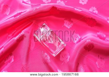 Small bottle of perfume over pink background