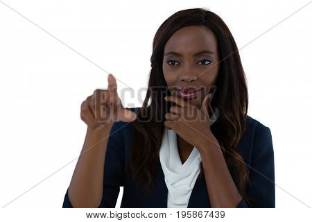 Confused businesswoman with hand on chin using interface screen against white background