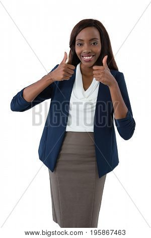 Portrait of smiling businesswoman showing thumbs up while standing against background