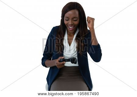 Happy businesswoman playing video game while sitting against white background