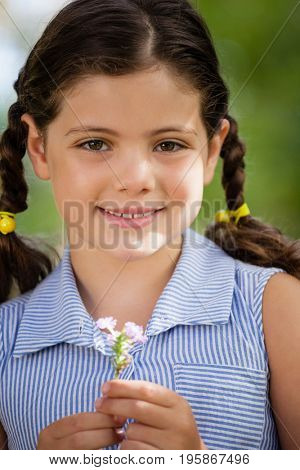 Portrait of smiling girl with braided hair holding flower at backyard