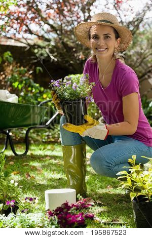 Portrait of smiling woman wearing hat holding potted plant while crouching on field in backyard