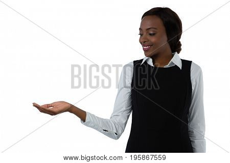 Smiling young woman looking at hand while standing against white background