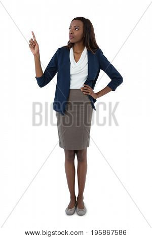 Businesswoman with hand on hip gesturing while giving presentation against white background