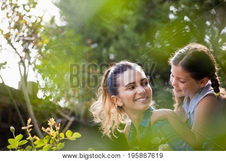 Happy mother piggybacking cute daughter in backyard on sunny day