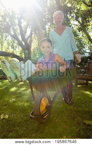 Smiling grandmother pushing granddaughter sitting in wheelbarrow at backyard