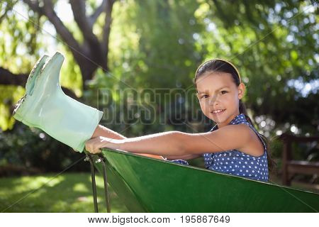 Portrait of girl wearing rubber boots sitting in wheelbarrow at backyard