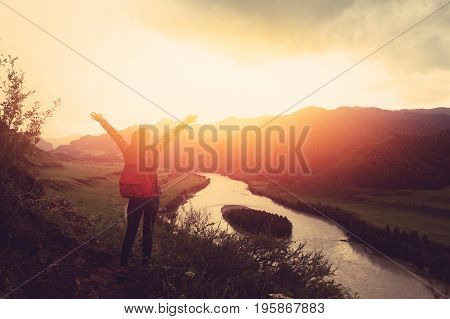 tourist girl stands on top of a mountain and has fun against backdrop of mountains and the river. The setting sun. Concept active rest. Space for text