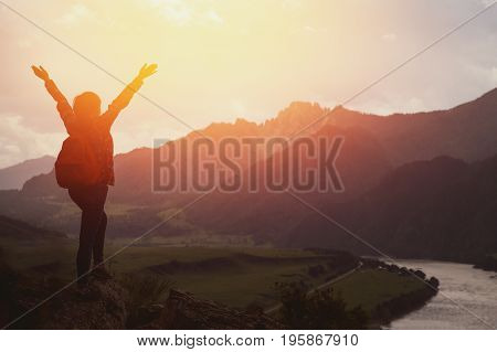 tourist girl in a plaid shirt and with a backpack standing on top of the mountain and having fun against the backdrop of mountains, rivers. The setting sun. Concept active rest. Space for text