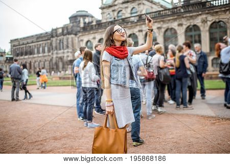 Young smiling woman photographing with smartphone while visiting with tourist group the old palace in Dresden city, Germany