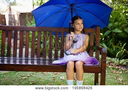 Girl sitting with blue umbrella on wooden bench at backyard