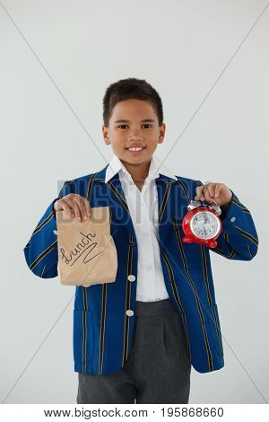 Portrait of schoolboy holding alarm clock and disposable lunch bag against white background