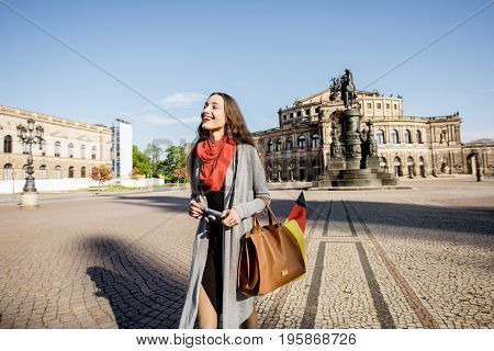 Lifestyle portrait of a young woman tourist walking with bag and german flag in front of the Opera house in Dresden city, Germany