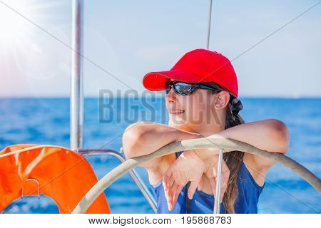 Girl captain on board of sailing yacht on summer cruise. Travel adventure, yachting with child on family vacation. Kid clothing in sailor style, nautical fashion.