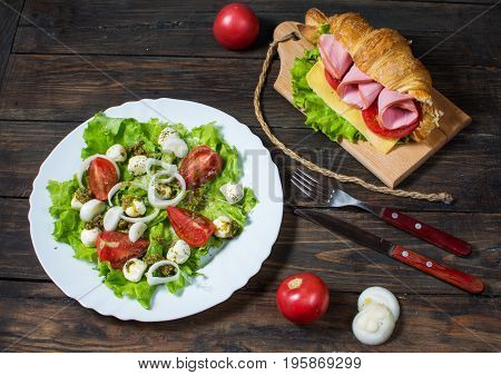 Light and hearty spring breakfast. Croissant with ham, cheese, fresh tomatoes and salad with Mozzarella on a wood table.