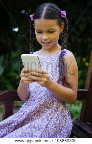 Girl using smartphone while sitting on bench at garden