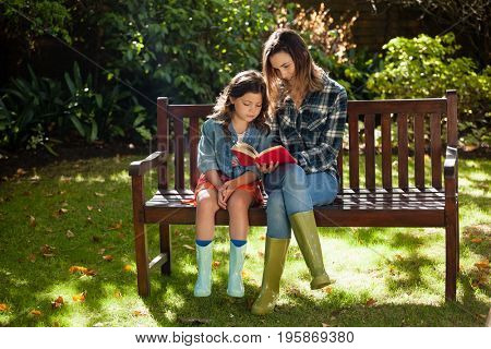 Woman reading book to daughter while sitting on wooden bench at backyard