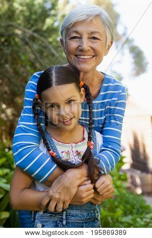 Portrait of smiling senior woman embracing granddaughter at backyard