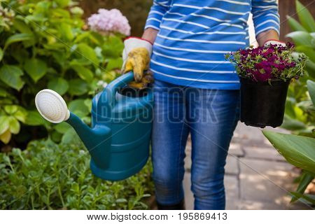 Midsection of senior woman holding watering can and flower pot amidst plants at backyard