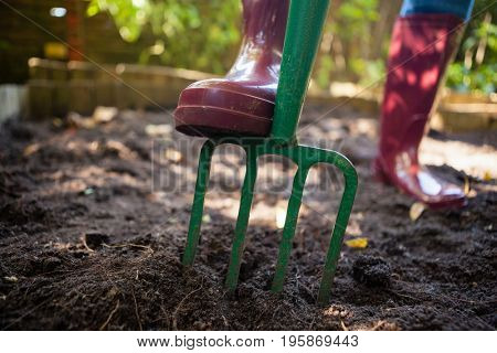 Low section of senior woman standing by garden fork on dirt at backyard