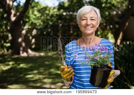 Portrait of senior woman holding potted plant and trowel at backyard