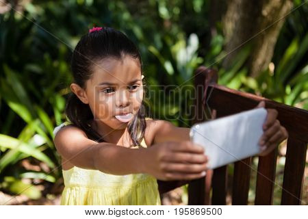 Girl sticking out tongue while taking selfie on wooden bench at backyard