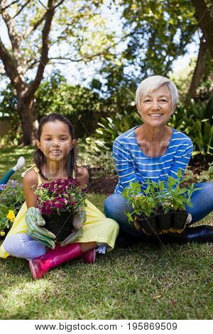 Portrait of smiling granddaughter and grandmother holding plants sitting with crossed legs at backyard