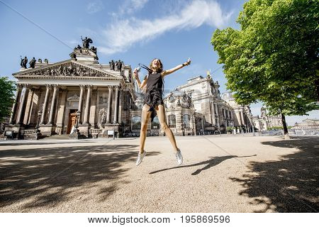 Young and happy woman touirst jumping in front of the old university building in Dresden, Germany
