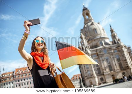 Young elegant woman tourist making selfie photo with german flag in front of the famous church in Dresden city, Germany