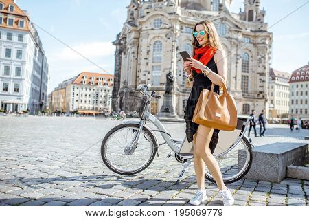 Young woman standing with phone and bag near the bicycle on the Neumarkt square in Dresden, Germany